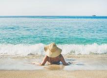 Hög kvinnaturist i bikinin som ligger på sand som tycker om havet arkivfoto
