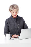 Hög kvinnlig arbetare som använder en bärbar dator Royaltyfri Foto