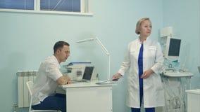 Hög kvinnlig doktor som delar ansvar mellan det medicinska laget arkivfilmer