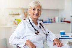 Hög kvinnlig doktor som ler på kameran royaltyfri bild