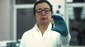 Hög kvinnlig forskare som arbetar med blodprövkopior på laboratoriumet stock video