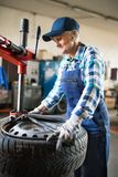 Hög kvinnlig mekaniker som reparerar en bil i ett garage arkivbilder