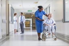 Hög kvinnlig patient i rullstol & sjuksköterska i sjukhus Royaltyfri Fotografi