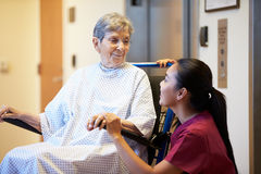 Hög kvinnlig patient som skjuts i rullstol av sjuksköterskan Fotografering för Bildbyråer