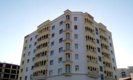 Hög löneförhöjningbyggnad som har stora lägenheter med sikt för främre höjd royaltyfria foton