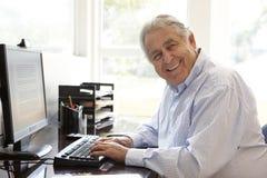 Hög latinamerikansk man som hemma arbetar på datoren Arkivfoto