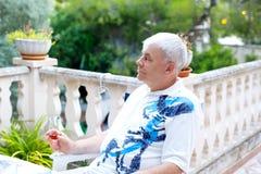 Hög man av 60 år som dricker exponeringsglas av rosa vin på semestrar Pensionerad man som tycker om varm sommarafton Royaltyfria Bilder
