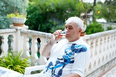 Hög man av 60 år som dricker exponeringsglas av rosa vin på semestrar Pensionerad man som tycker om varm sommarafton royaltyfri fotografi