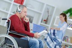 Hög man i rullstol med hjälpvårdare Royaltyfri Bild