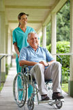 Hög man i rullstol med sjuksköterskan Arkivbild