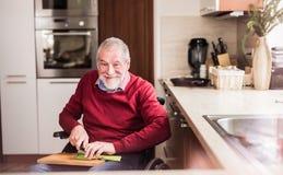 Hög man i rullstolmatlagning i köket royaltyfri foto