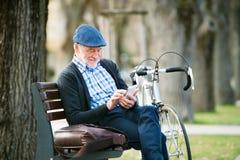 Hög man med cykeln i stad och att rymma den smarta telefonen som smsar Royaltyfria Bilder