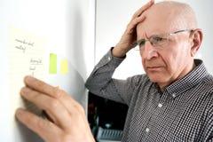 Hög man med demens som ser anmärkningar arkivfoton
