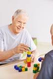 Hög man med demens som spelar med tegelstenar royaltyfri foto