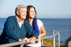Hög man med den vuxna dottern som ser havet Arkivfoton