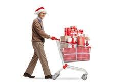 Hög man med en Santa Claus hatt som skjuter en shoppa vagn med gåvor och ser kameran arkivfoton