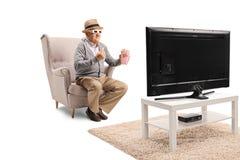 Hög man med exponeringsglas 3d och popcorn som sitter i en fåtölj och en watchinTV royaltyfri foto