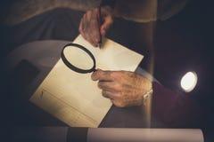 Hög man med förstoringsglashandstil på papper close upp arkivfoto