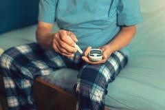 Hög man med glucometer som kontrollerar nivån för blodsocker arkivfoton