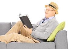 Hög man med hatten på en soffa som läser en roman royaltyfri foto