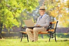 Hög man med hattsammanträde på en bänk och arbete på bärbara datorn in royaltyfri bild