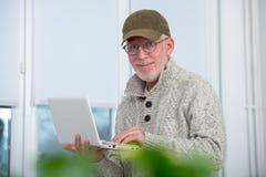 Hög man med locket genom att använda bärbara datorn hemma arkivfoto