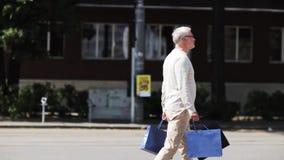 Hög man med shoppingpåsar som går i stad arkivfilmer