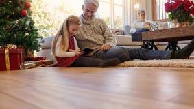 Hög man med sondottern som hemma använder den digitala minnestavlan royaltyfria bilder