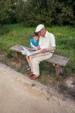 Hög man och barn som utomhus läser en tidning Arkivbild