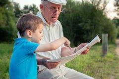 Hög man och barn som utomhus läser en tidning arkivfoton