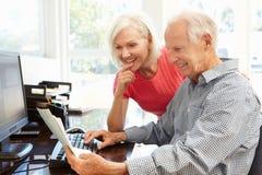Hög man och dotter som hemma använder datoren royaltyfri fotografi