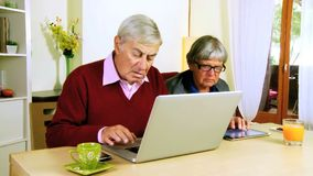 Hög man och kvinna med datoren arkivfilmer