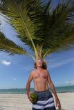Hög man på stranden med en kokosnöt arkivfoto