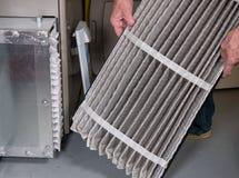 Hög man som ändrar ett smutsigt luftfilter i en HVAC-panna arkivbild