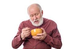 Hög man som äter från oragnebunken som isoleras på vit Royaltyfri Fotografi