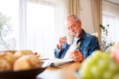 Hög man som äter frukosten och hemma gör korsord arkivbild