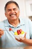 Hög man som äter frukt royaltyfria bilder