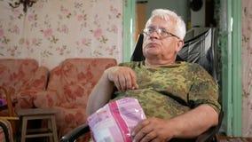 Hög man som äter havrepinnar och håller ögonen på TV Sitter i en läderfåtölj med exponeringsglas stock video