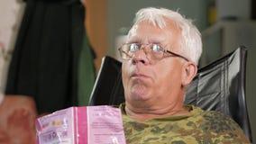 Hög man som äter havrepinnar och håller ögonen på TV Sitter i en läderfåtölj med exponeringsglas arkivfilmer