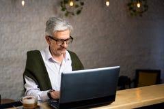 Hög man som använder bärbara datorn och har kaffe i stången fotografering för bildbyråer
