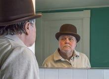 Hög man som bär ett brunt derby i badrumspegeln arkivbild