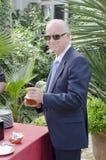 Hög man som dricker alkohol i coctail Arkivfoto