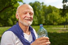 Hög man som dricker flaskan av vatten i sommar fotografering för bildbyråer