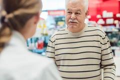 Hög man som får rådgivning från apotekare i apotek arkivfoton