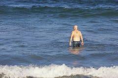 Hög man som går för ett bad i havet fotografering för bildbyråer