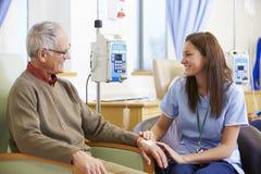 Hög man som genomgår kemoterapi med sjuksköterskan Arkivfoto