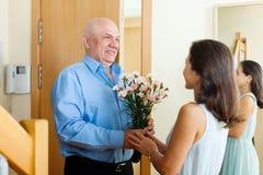 Hög man som ger gruppen av blommor till kvinnan Fotografering för Bildbyråer