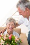 Hög man som ger hans partner en bukett av blommor som ler på kameran Arkivfoton