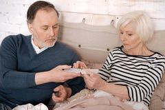 Hög man som ger preventivpillerfallet till hans sjuka fru royaltyfri fotografi