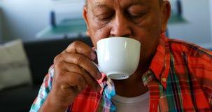 Hög man som har kopp te på avgånghemmet 4k stock video